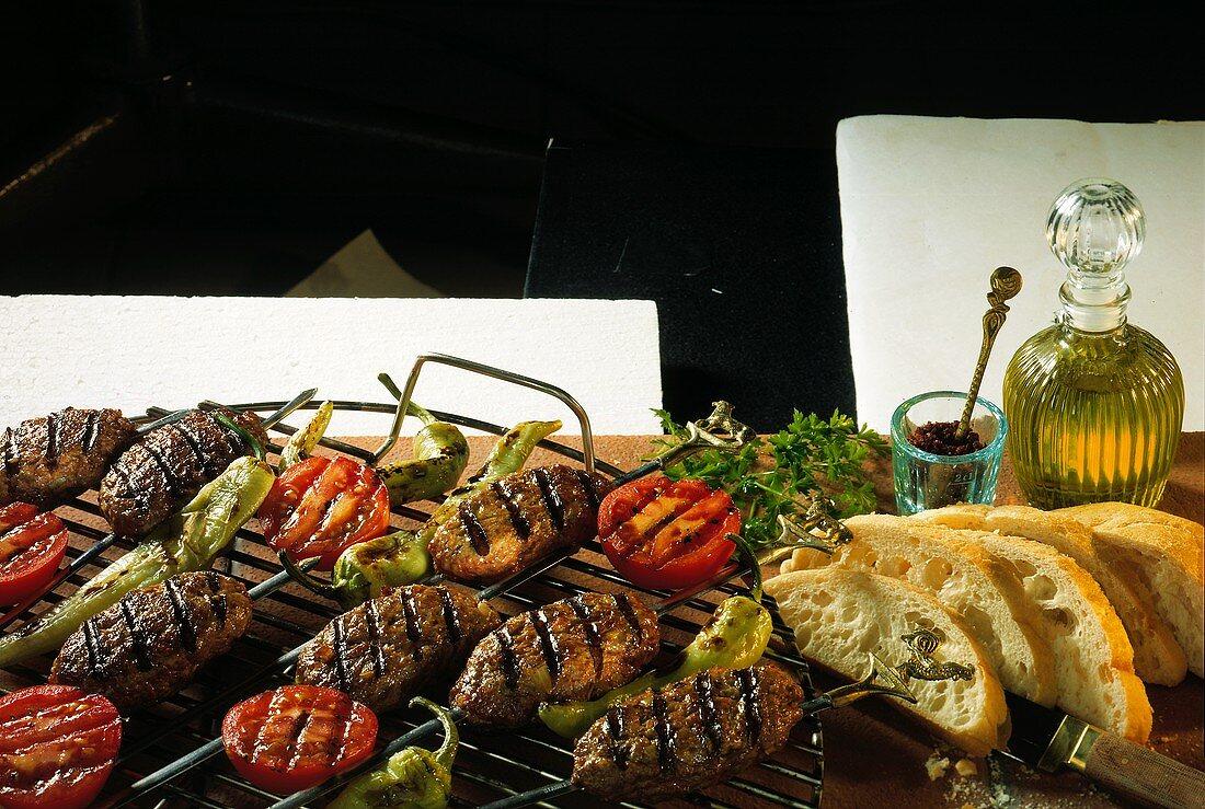 Adana-Spiesse mit Tomatenscheiben; gegrillte Peperoni