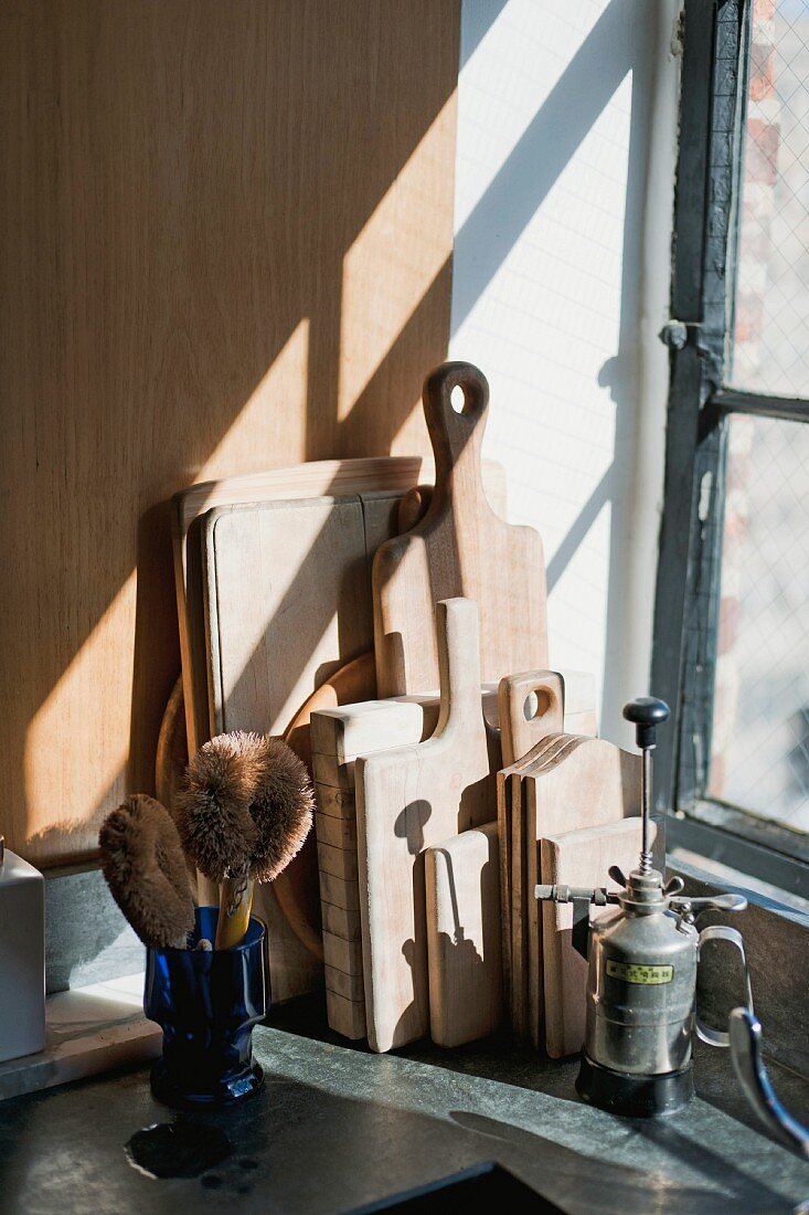A collection of cutting boards and a blow torch in front of an old window