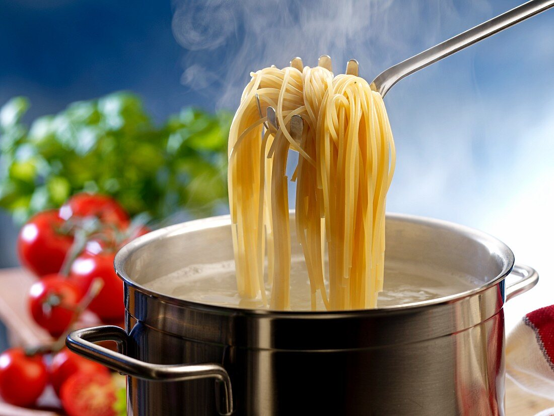 Cooked spaghetti on a spaghetti spoon being removed from a pot