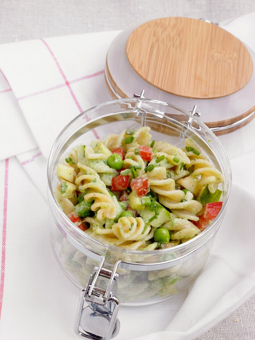 Pasta salad with vegetables in a jar for a picnic