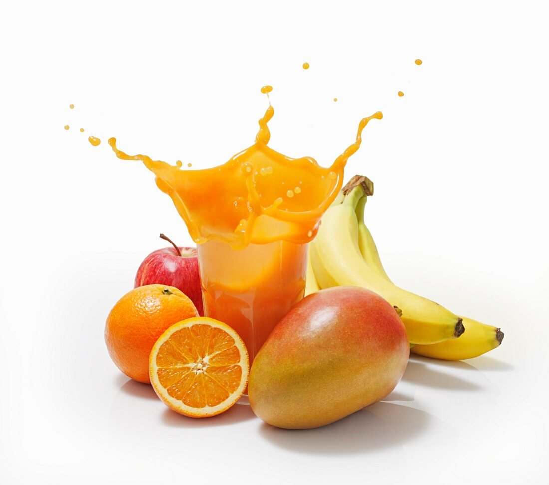 A splash of juice in a glass surrounded by oranges, bananas, mango and apple