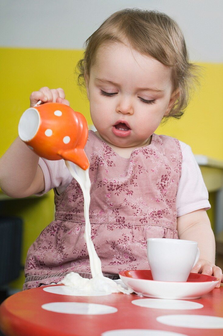 Young girl spilling milk on table