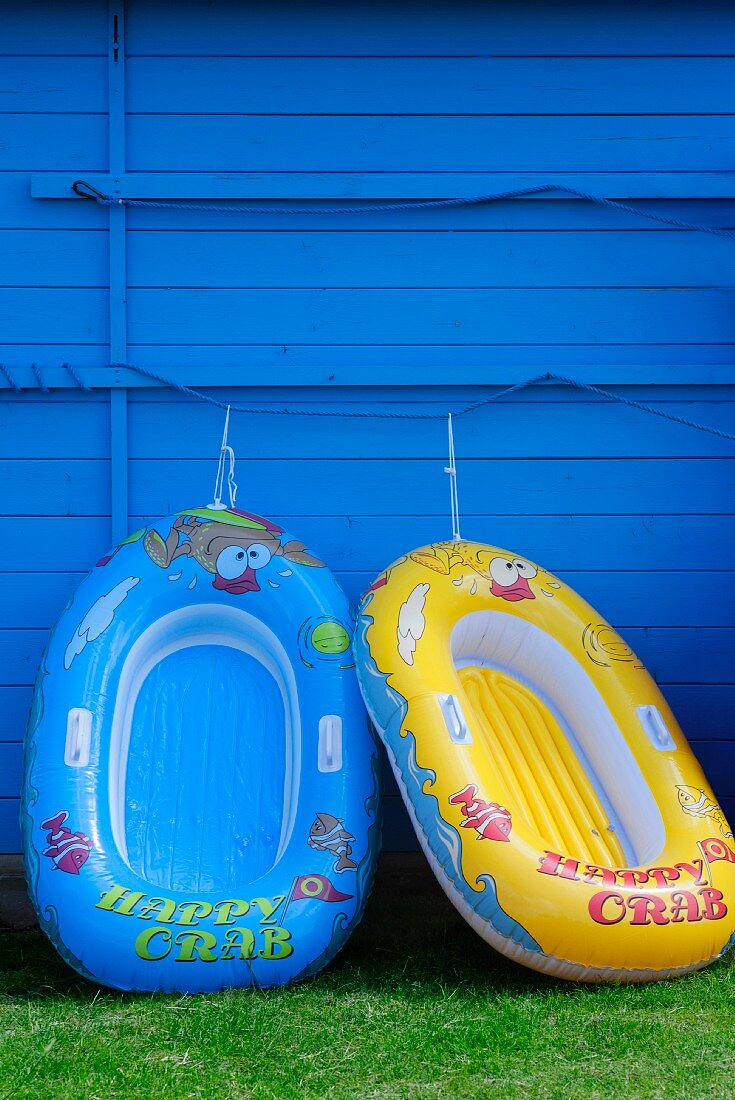 Two rubber dinghies on a blue wooden wall