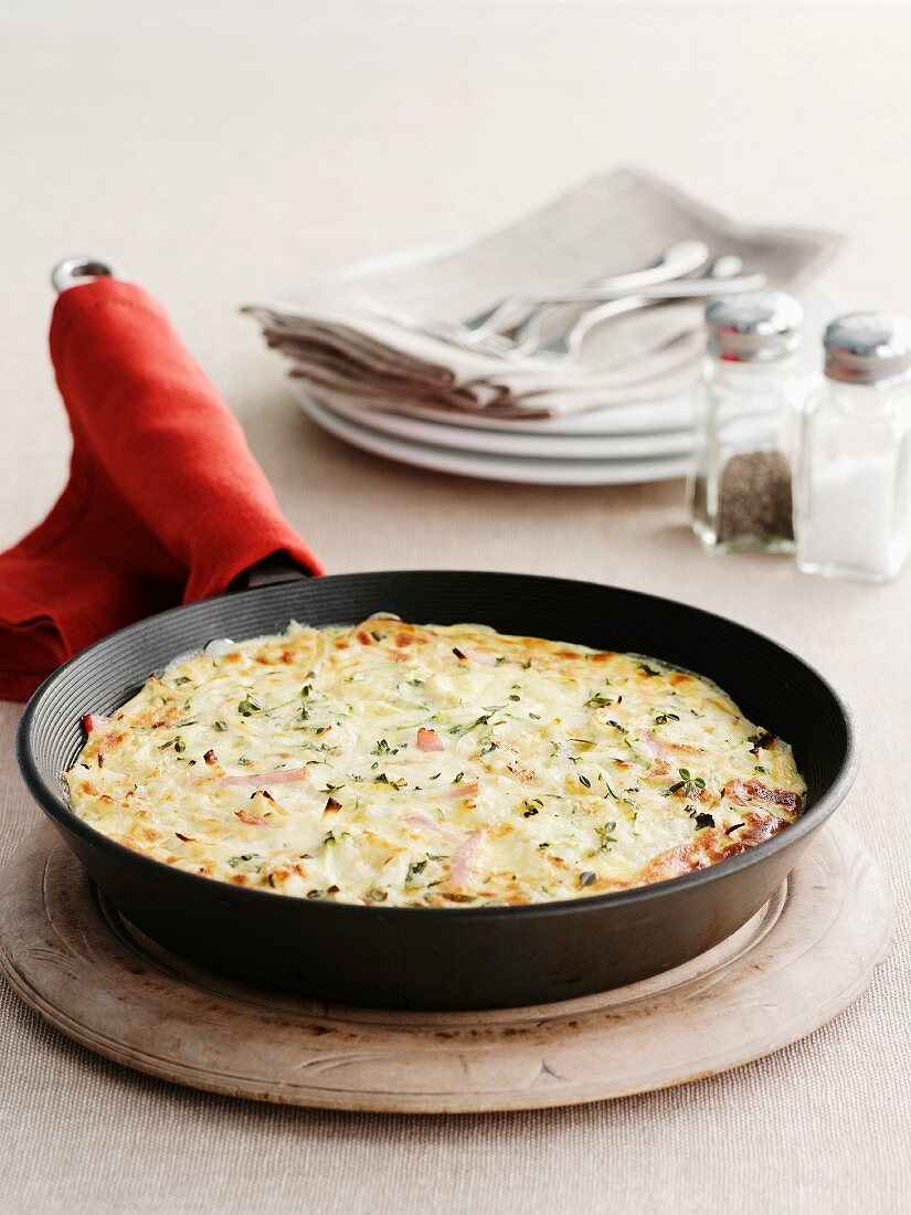 Omelette with ham and herbs in a frying pan on a wooden board
