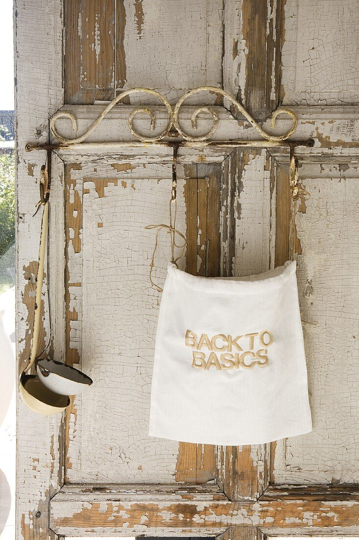 Linen sack and soup ladles hanging on weathered window shutter