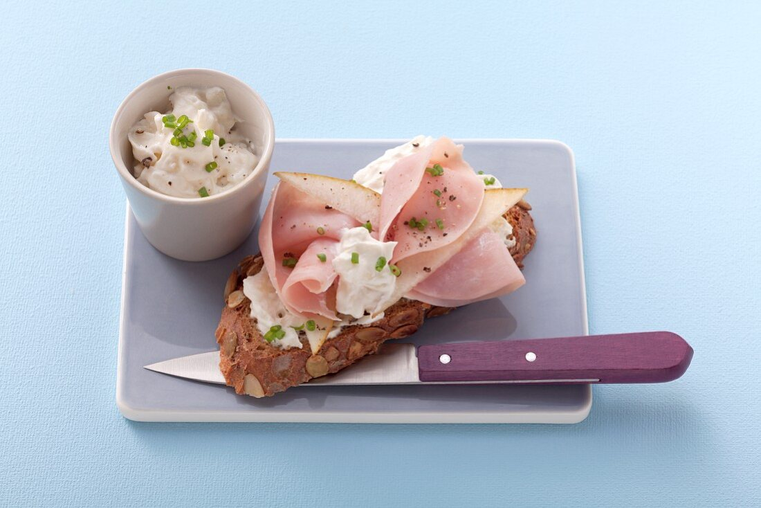 Pumpkin seed bread topped with cream cheese, ham and pears