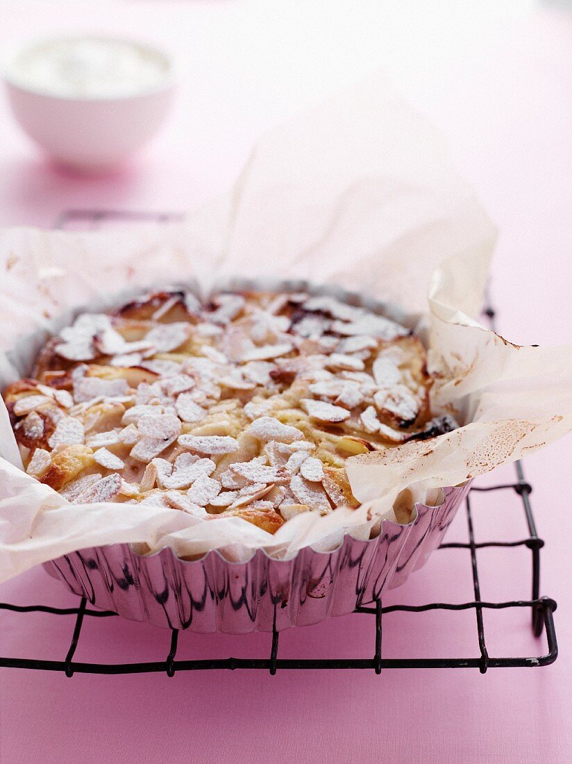 A whole pear and almond tart in a baking dish