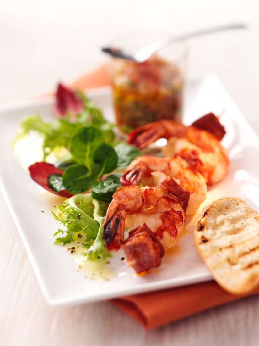 A prawn kebab with bacon and a side salad