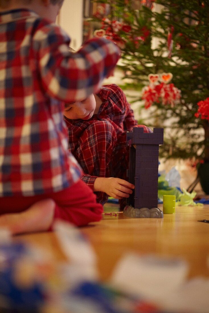 Two children unwrapping Christmas presents