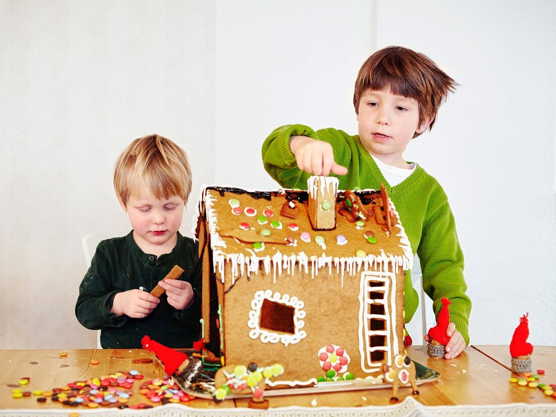 Two boys decorating a gingerbread house