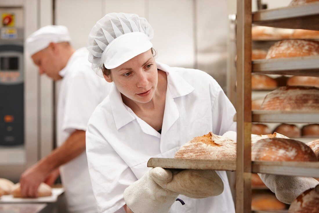 A woman placing a tray of freshly baked bread on a shelf