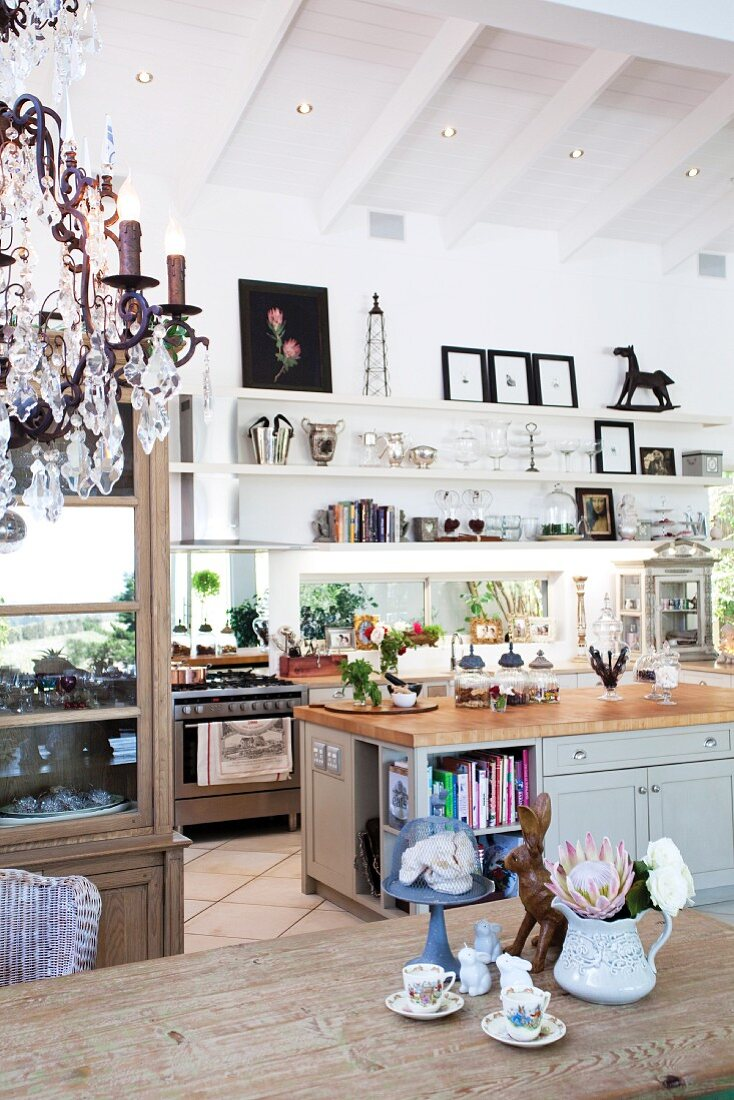 View into kitchen with central island and open wall-mounted shelves