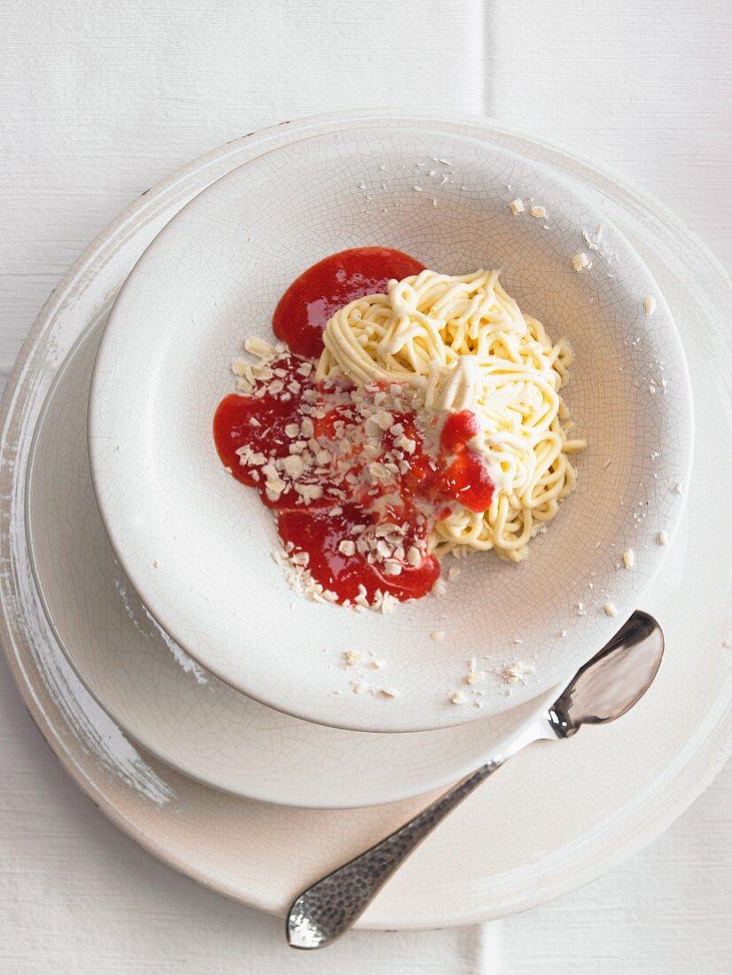 Spaghetti ice cream sundae with fruit sauce and nuts