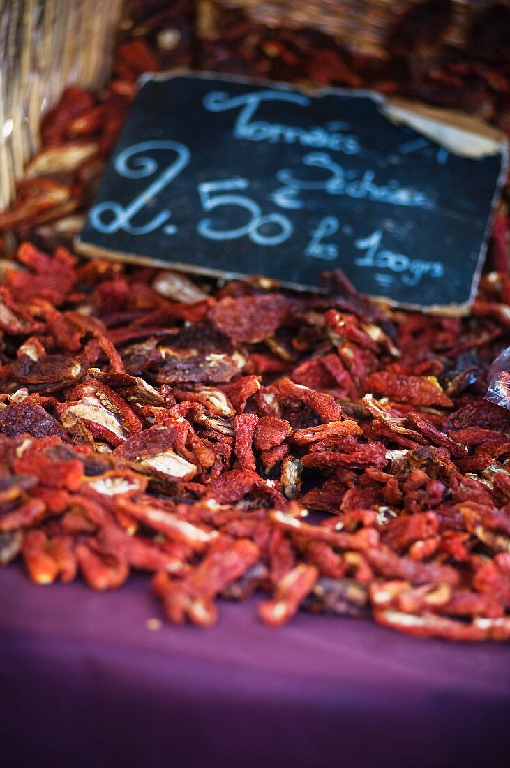 Dried tomatoes on a market stall with a price label
