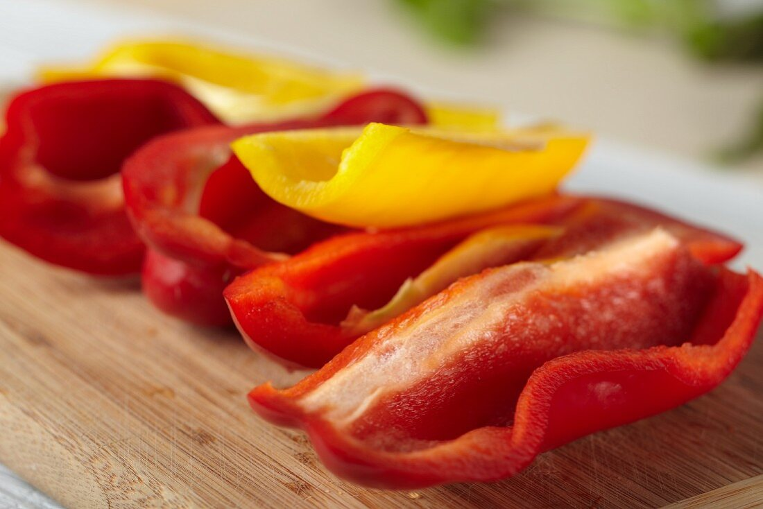 Fresh Red and Yellow Bell Peppers on a Cutting Board