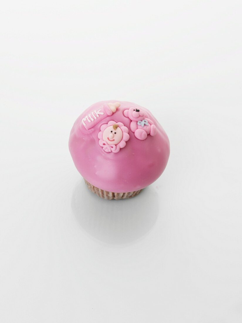 A pink cupcake decorated with baby motifs