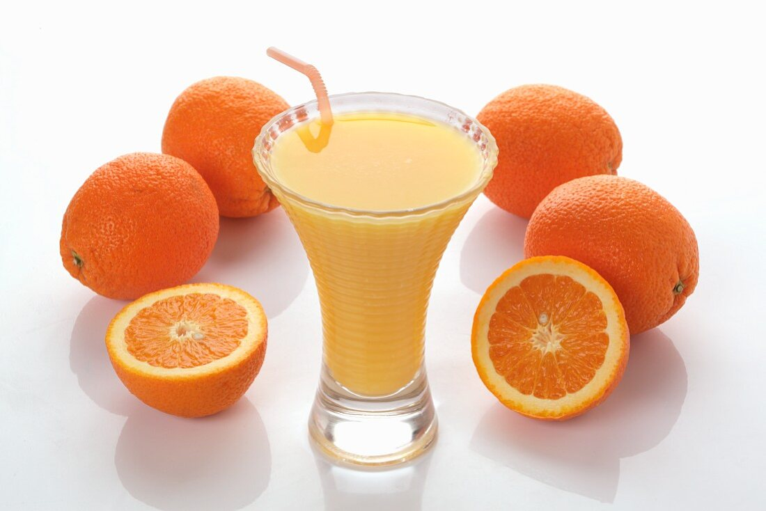 An orange smoothie and fresh oranges