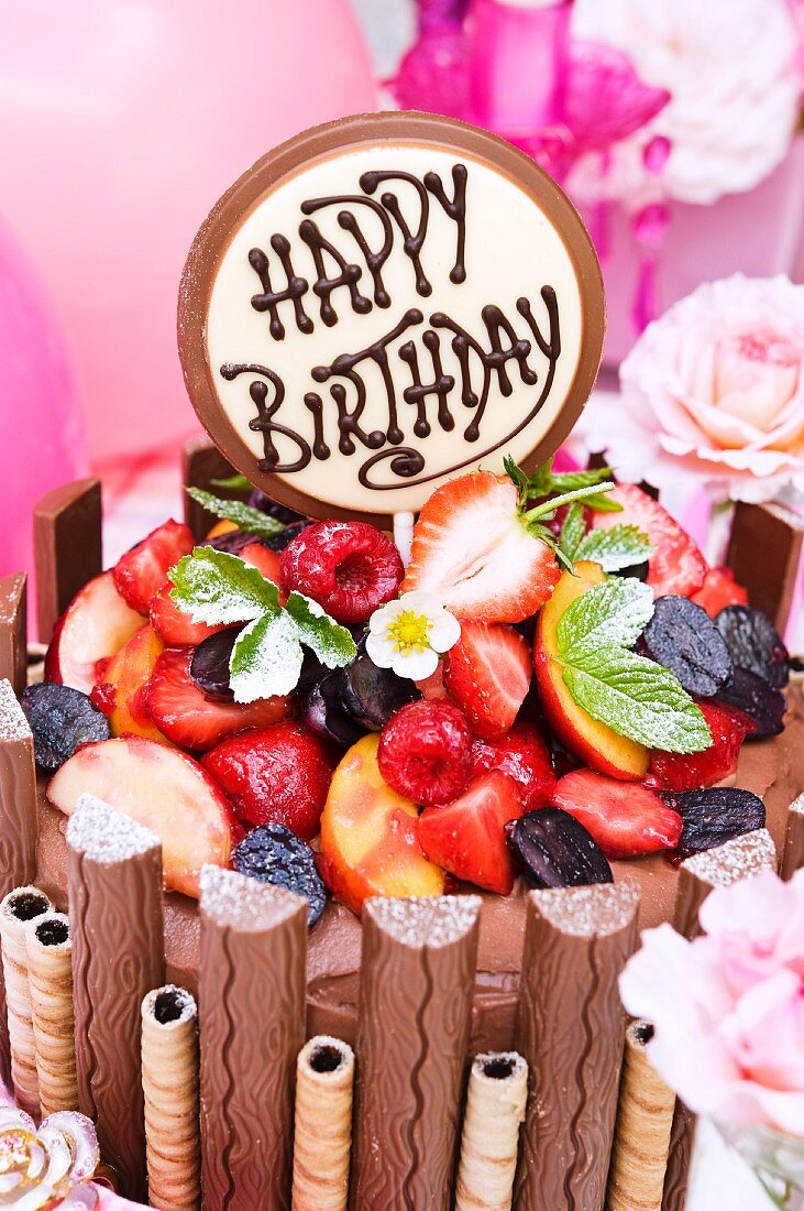 A chocolate cake with chocolate bars, wafer rolls and summer fruits for a birthday
