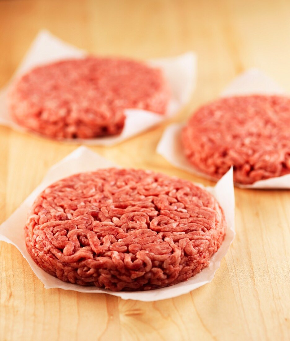 Three raw burgers on pieces of paper