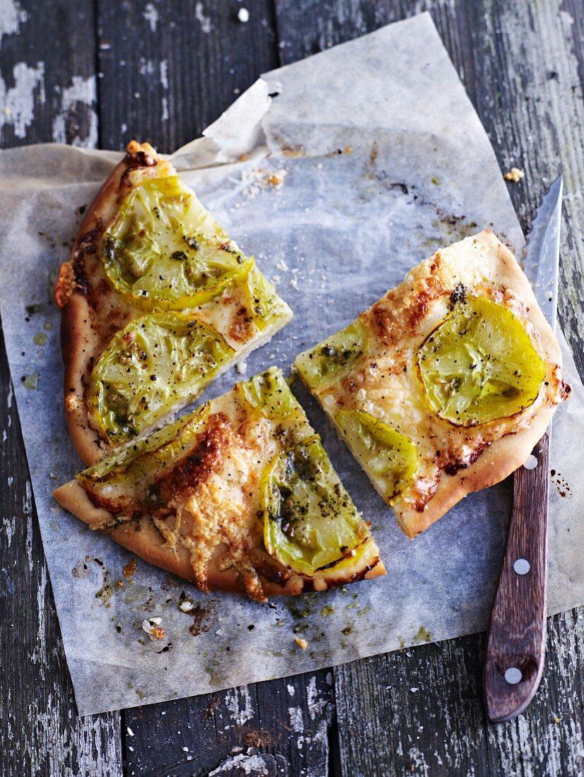 Green tomato pizza, cut into pieces
