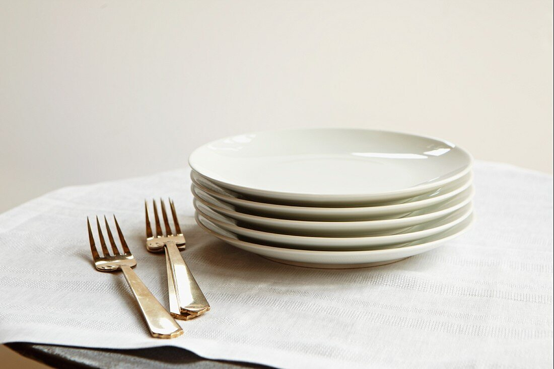 Stack of White Plates and Forks on Linen