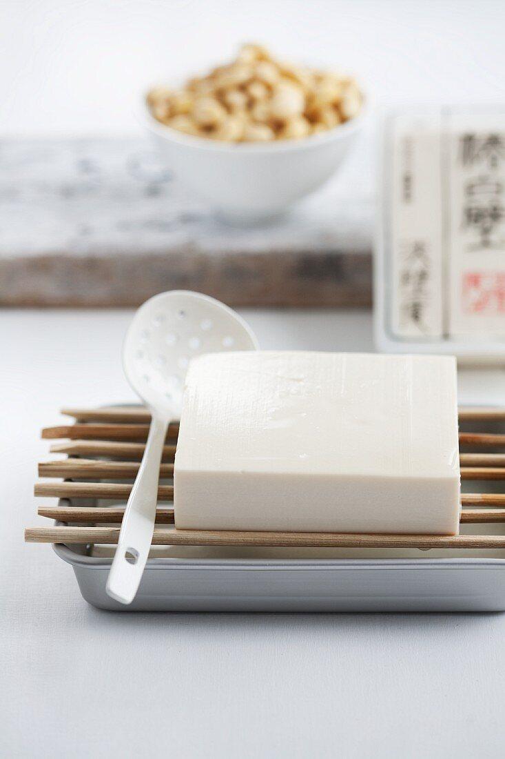 Silken tofu draining over an aluminium tray