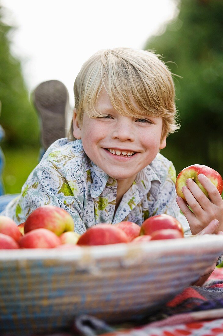 A blond boy with apples