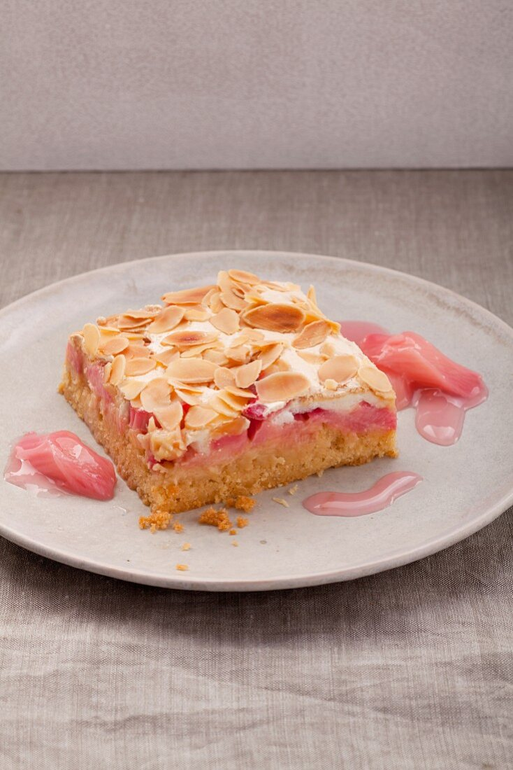 A piece of rhubarb cake with meringue and almonds on a white plate