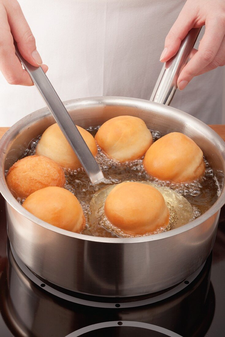 Doughnuts being fried in a pan and being removed with a slotted spoon