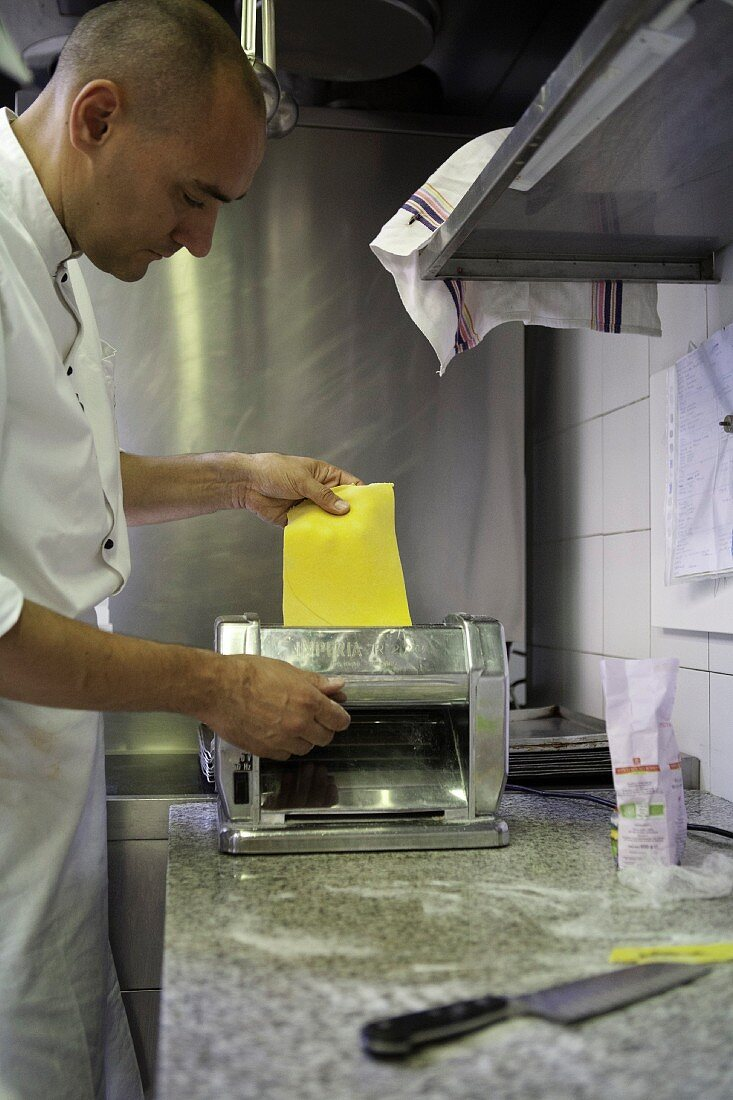 A cook passing pasta dough through a pasta machine