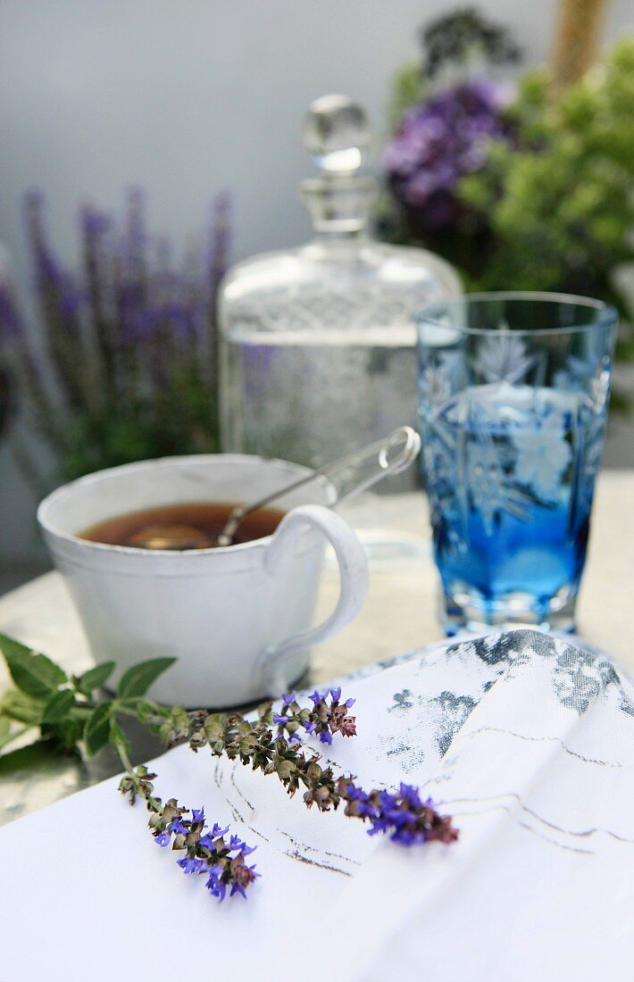 A cup with egg-shaped tea infuser and mint leaves; a blue crystal glass and a carafe of water are blurred in the background