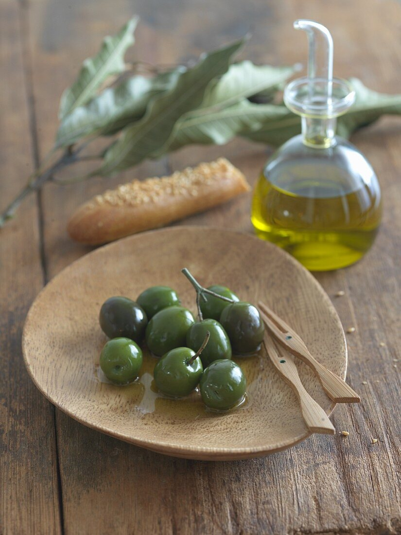 Green Olives with Olive Oil on a Wooden Dish; Carafe of Olive Oil
