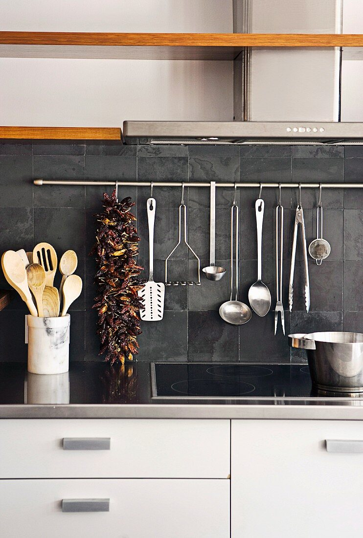 Various kitchen utensils hanging against dark grey tiles below extractor hood
