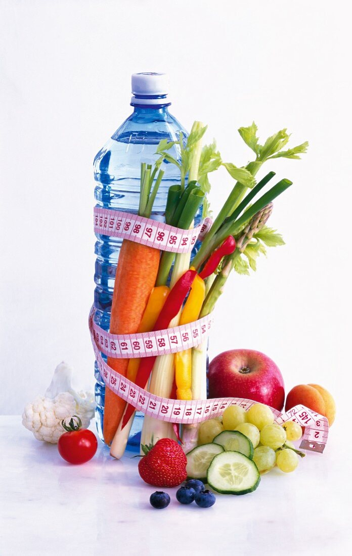 A bottle of water with a measuring tape, vegetables and fruit
