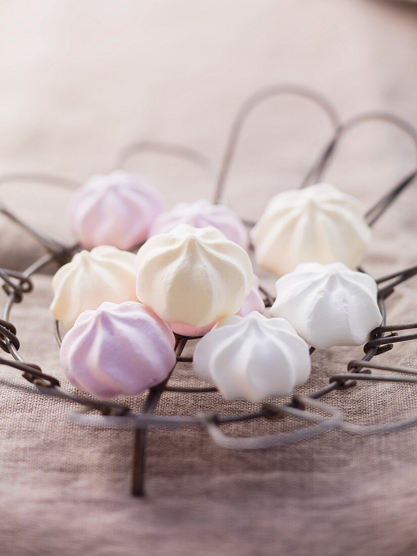 Pastel-coloured meringues on a wire rack