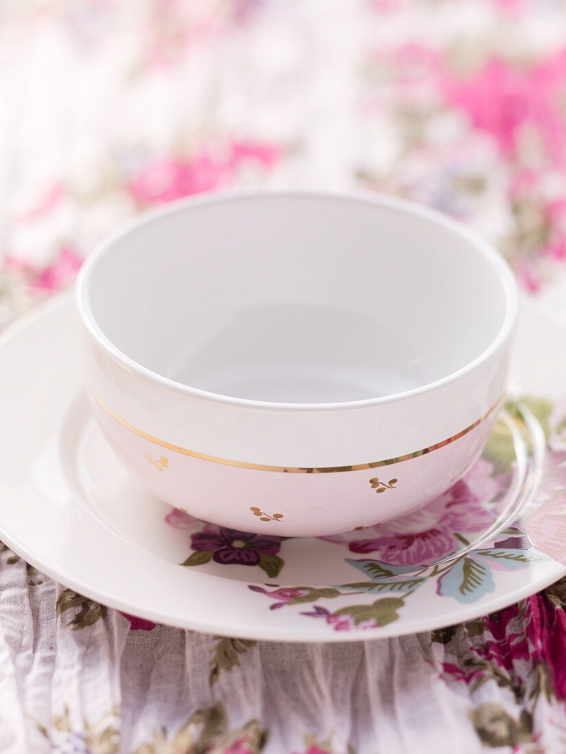 A floral-patterned plate and a white bowl on a floral table cloth