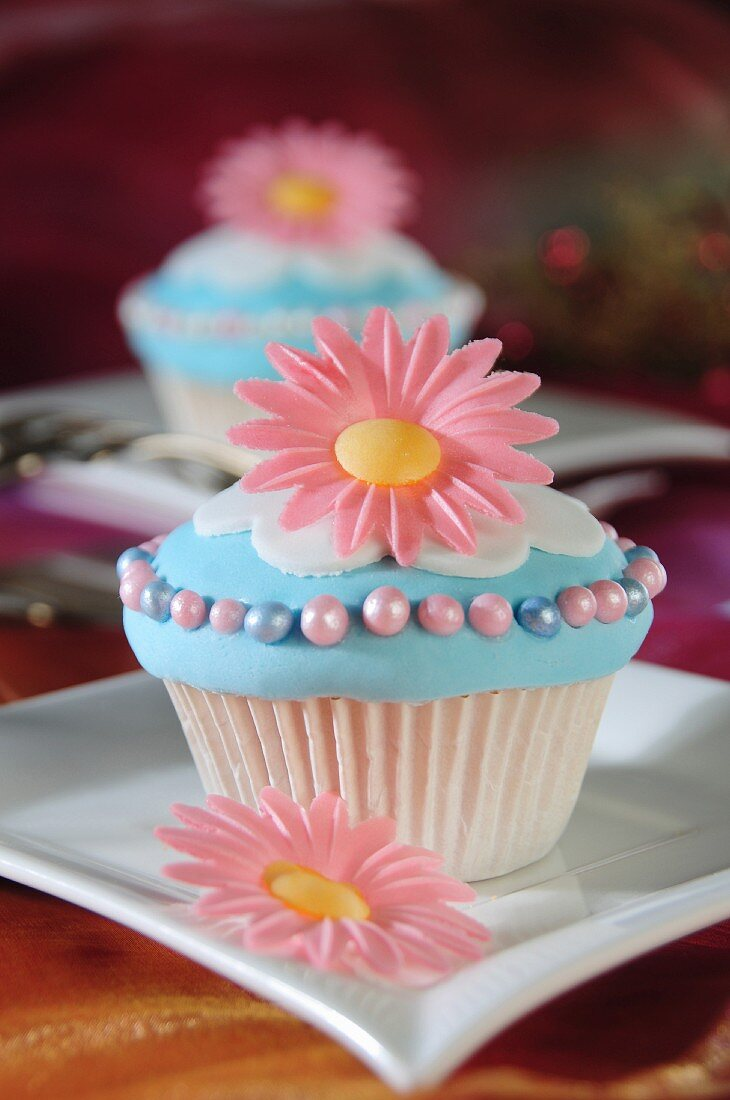 Light blue cupcakes decorated with pink flowers and sugar balls