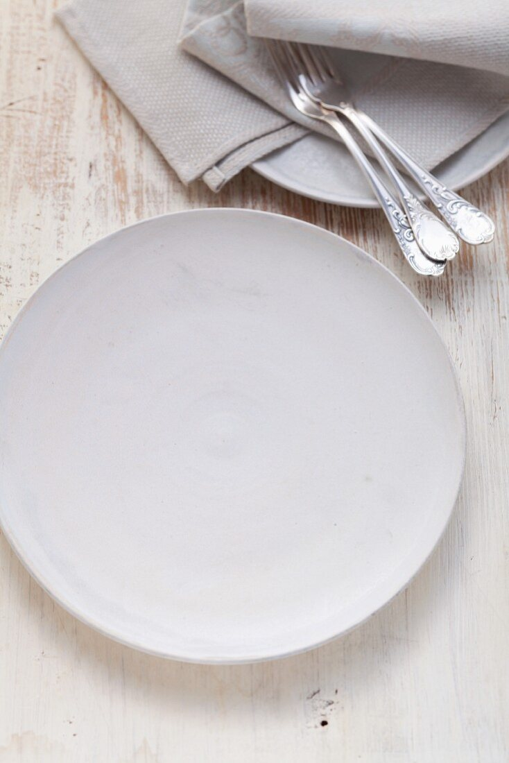 A simple white porcelain plate with forks and napkins next to it