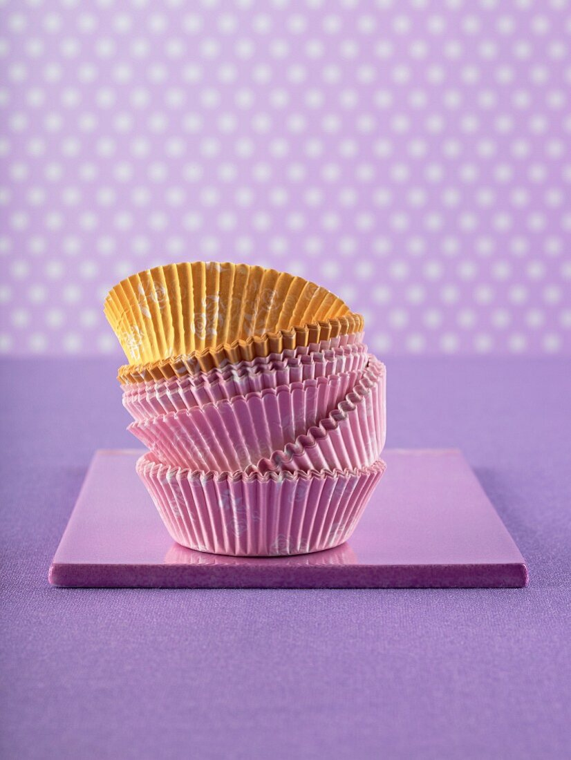 Pink and yellow muffin cases against a purple surface
