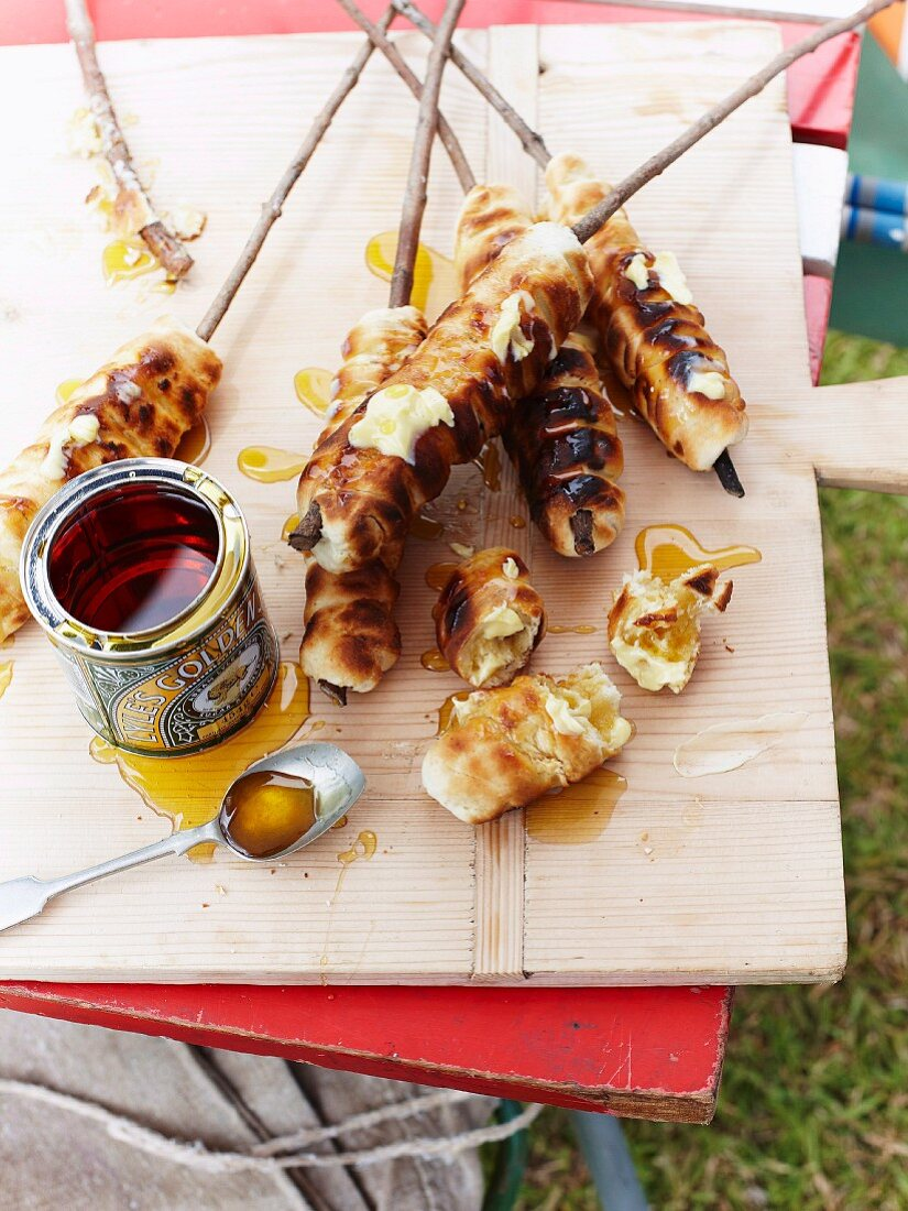 Campfire bread with syrup on a table outdoors