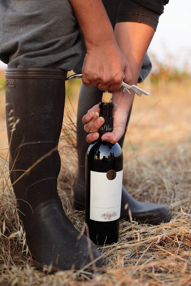 A woman opening a bottle of red wine in a field