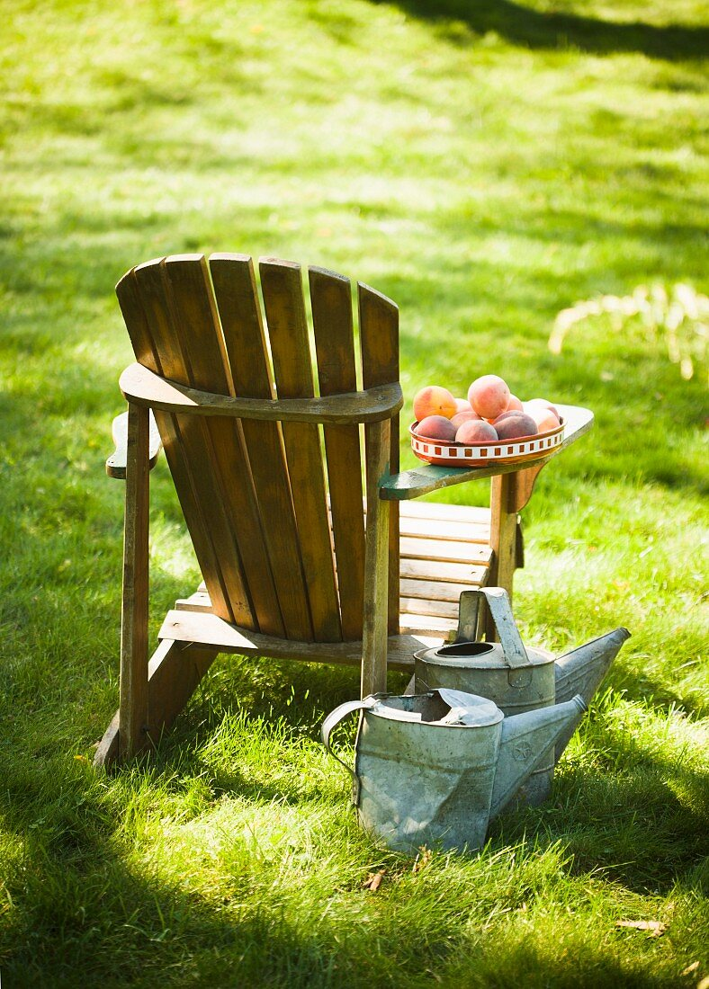 Wooden Adirondack Chair with Peaches on the Arm; Two Metal Watering Cans
