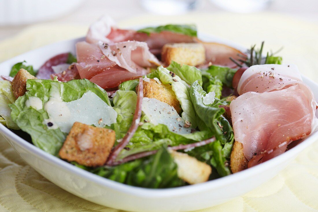Salad with Prosciutto, Shaved Parmesan and Croutons; In a Bowl