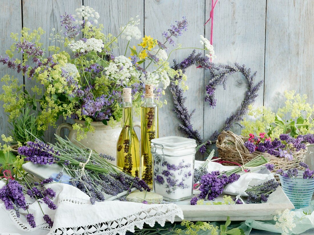 An arrangement of lavender: a heart-shaped lavender wreath, a jar of lavender sugar, two bottles of lavender and olive oil, wild chervil and lady's mantle