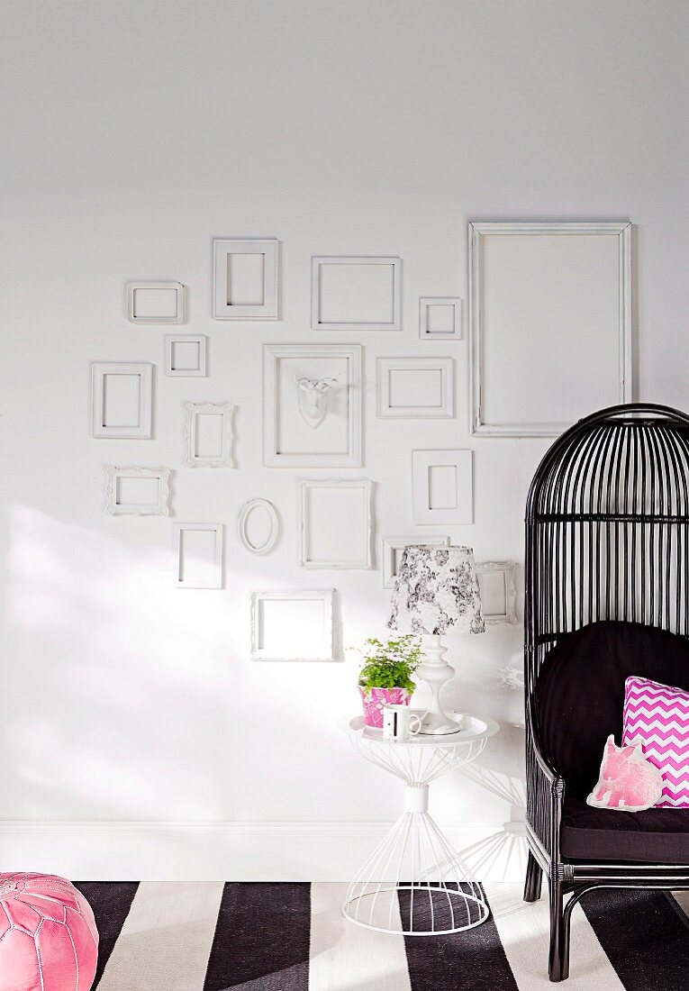 White picture frames on a white wall next to a black wicker chair