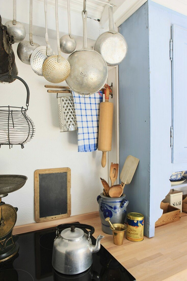 Modern meets old in a simple kitchen with a ceramic hob and antique cooking utensils