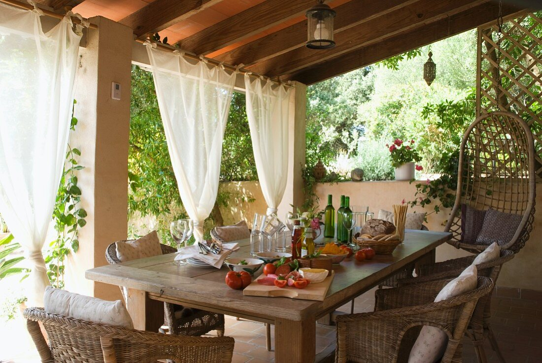 A table laid for a meal, with rattan chairs, on the veranda
