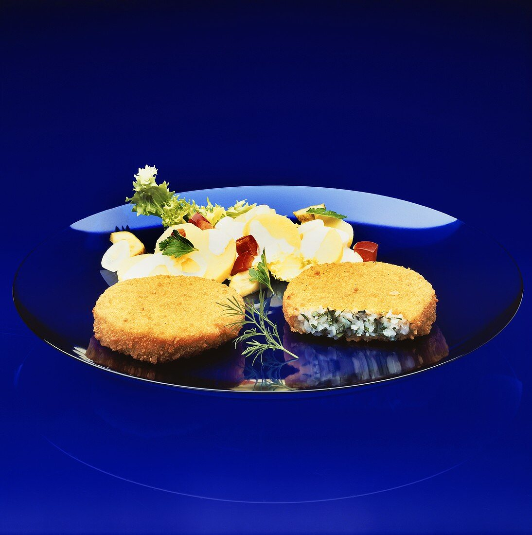Two baked, breaded Fishcakes with potato salad on blue Plate