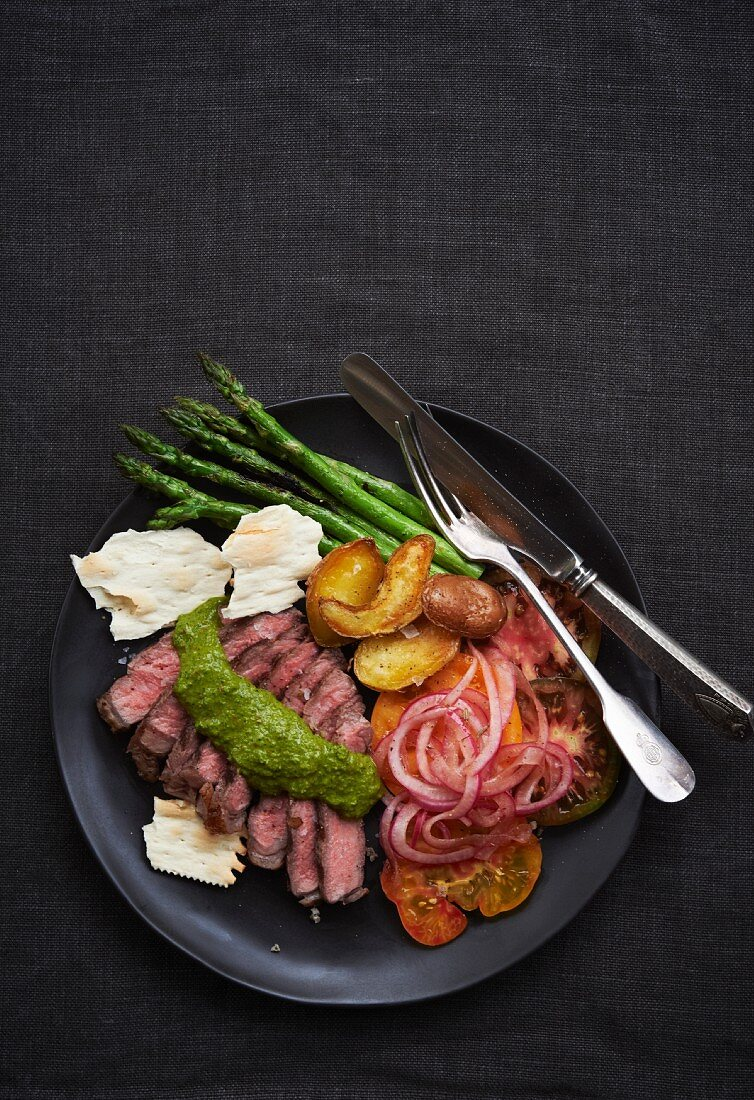 Sliced Beef Tenderloin with Chimichurri Sauce, Asparagus, Potatoes, Tomatoes and Pickled Red Onions; From Above