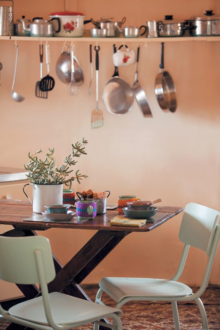 Pots, pans and kitchen utensils on wall-mounted shelf above dining table in kitchen